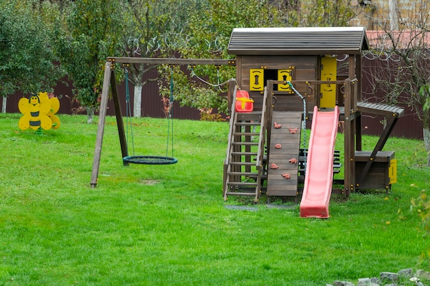 Wooden playground with plastic elements swings and slides for children in the garden