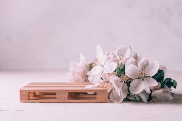 Wooden podium in form of pallet on light plaster surface with apple flowers. podium, pedestal or stage. mockup for cosmetic products