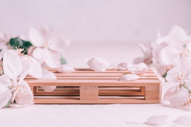 Деревянный подиум в виде поддона на светлой штукатурке с цветами яблони. подиум, пьедестал или сцена. мокап для косметической продукции