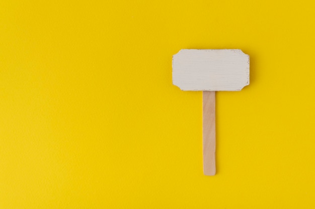 Wooden pointer on yellow background. information plate. wooden plate.