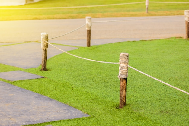 Wooden poles wrapped with rope use for block grass field