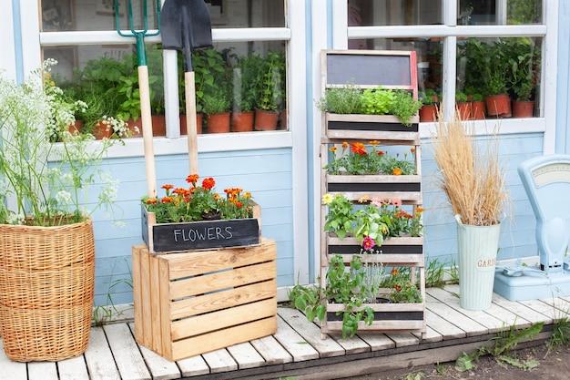 녹색 식물과 꽃이 있는 집의 나무 현관 정원 도구와 화분 꽃이 있는 집