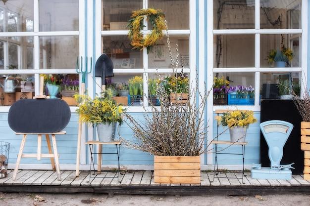 植物や枝の黄色いミモザと家の木製ポーチ。園芸工具、鉢植えの花のあるファサードの家。居心地の良い春の装飾ベランダ。ガーデニングのコンセプト。椅子付きの夏のベランダ。イースターの装飾家