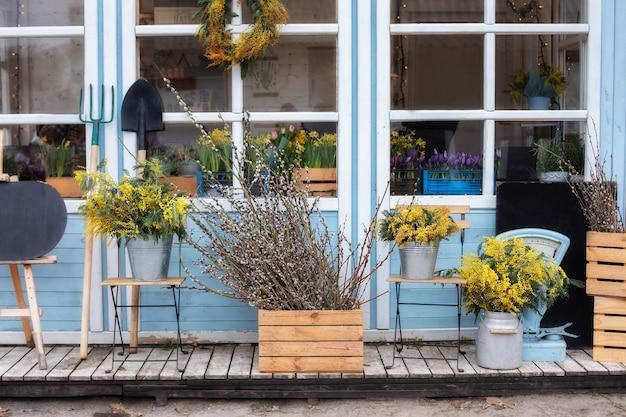 식물을 가진 집의 나무 현관. 정원 도구와 화분 꽃이있는 외관 집.