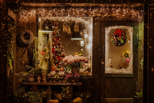 The wooden porch of the store decorated with christmas decoration with a wreath on the door