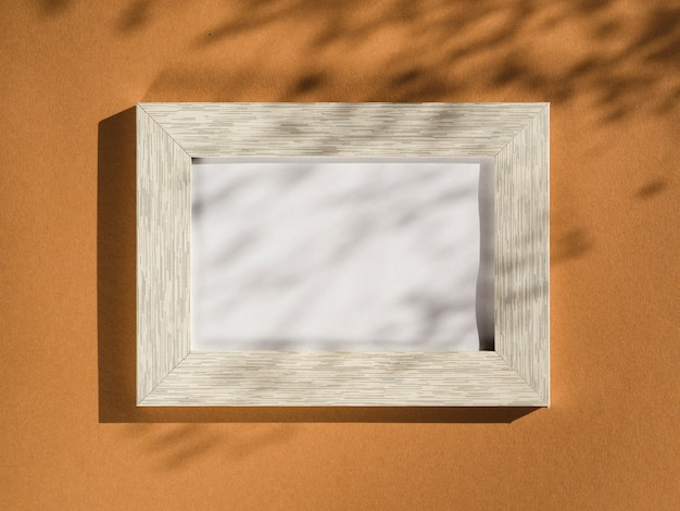 Wooden portrait frame on a beige background covered with leaf shadows