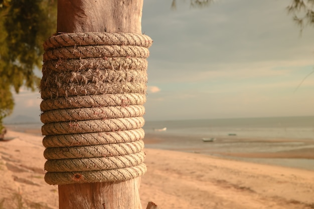 Wooden post with mooring ropes on the beach.