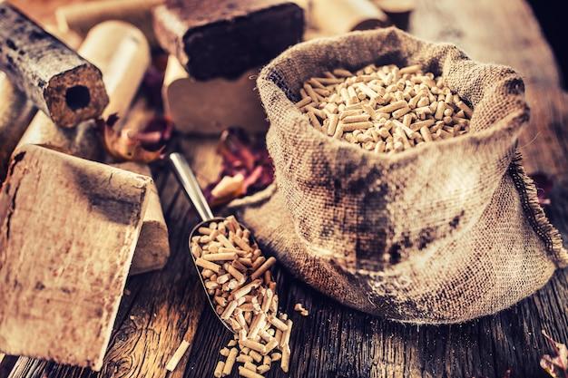 Деревянные прессованные пеллеты и брикеты из биомассы с осенними листьями.