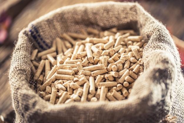 Деревянные прессованные гранулы из биомассы в старом мешке.