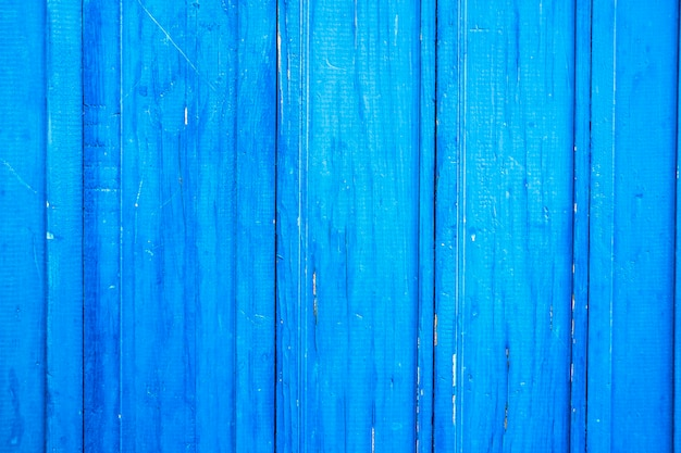 Wooden protection on all background, is painted light blue. old cracked blue paint on wood flooring.