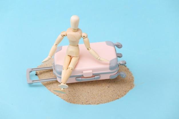 砂の島にある木製の人形とミニ旅行かばんスーツケース。旅行、ビーチでの休暇の概念