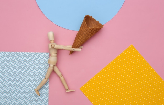 Деревянная марионетка, держащая вафельный рожок мороженого на цветном фоне.