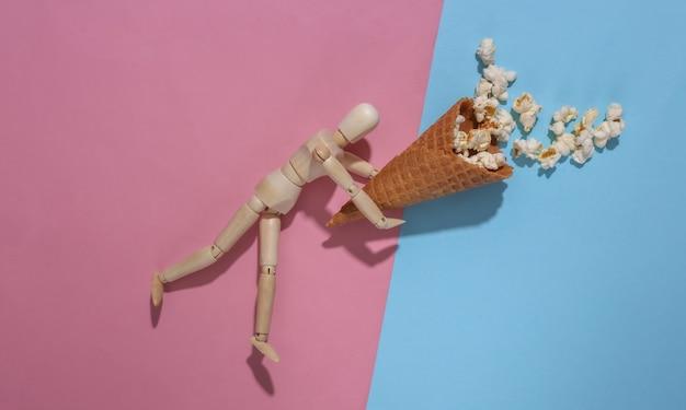 Деревянная марионетка, держащая вафельный рожок мороженого с попкорном на розовом синем фоне. вид сверху