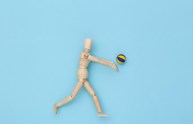 Wooden puppet plays volleyball with ball on blue background