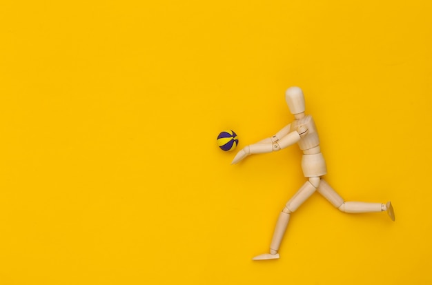 Wooden puppet plays volleyball with ball on yellow background