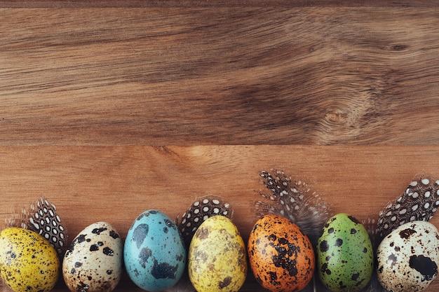 木製のウサギとイースターエッグ、フラットレイ、上面図、コピースペース。イースターのコンセプト。木製の背景にお祝いのイースターの装飾。レトロなスタイルの明るい背景。グリーティングカード。