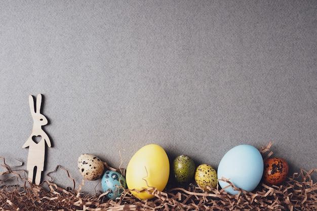 芝生の上の木製のウサギとイースターエッグ、フラットレイ、上面図、コピースペース。イースターのコンセプト。灰色の紙の背景にお祝いのイースターの装飾。レトロなスタイルの明るい背景。グリーティングカード。