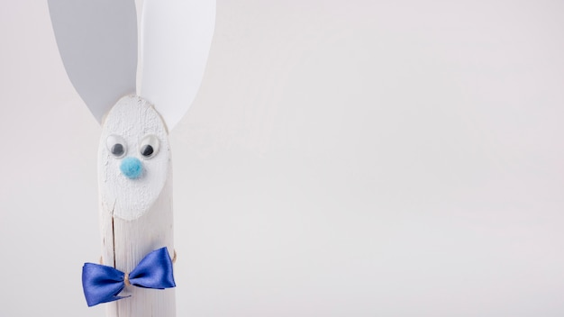 Wooden rabbit with paper ears on white background
