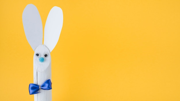 Wooden rabbit with paper ears on yellow background