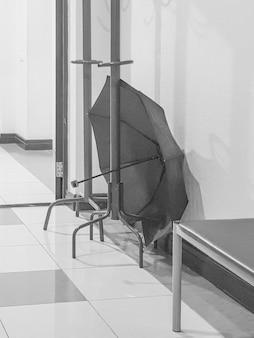 의료 클리닉 복도의 빈 방에 열린 우산이 있는 나무 선반 걸이, 수직, 흑백