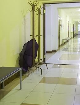의료 클리닉 복도의 빈 방에 열린 우산이 있는 나무 선반 걸이, 수직.