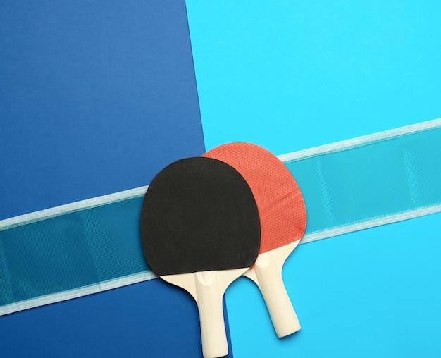 Деревянные ракетки для игры в настольный теннис и сетка на синем фоне