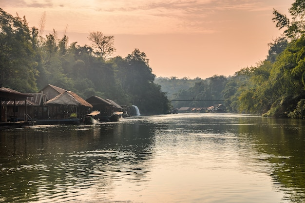 Wooden raft resort with waterfall flowing in river kwai at evening
