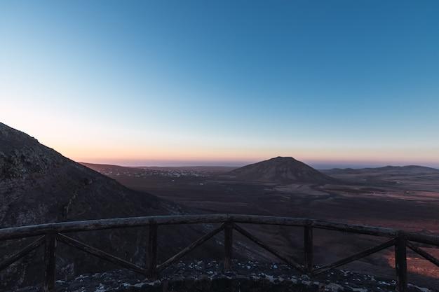 木製の手すりと日没時に美しい山々の景色