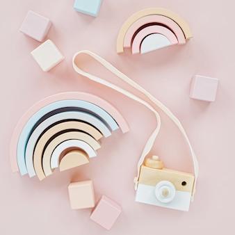 나무 무지개, 다채로운 블록 및 장난감 카메라. 파스텔 핑크 배경에 세련된 아기 장난감. 어린이를 위한 친환경 플라스틱 무료 장난감 액세서리. 평평한 평지, 평면도