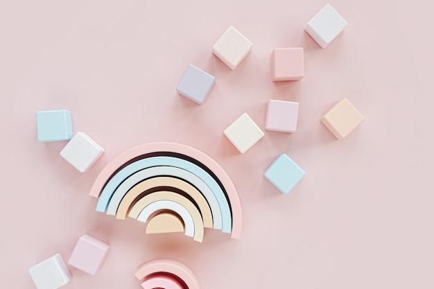 나무 무지개, 다채로운 장난감 블록. 파스텔 핑크 배경에 세련된 아기 장난감. 어린이를 위한 친환경 플라스틱 무료 장난감 액세서리. 평평한 평지, 평면도