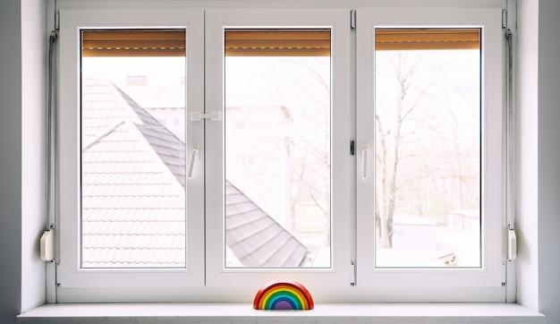 自宅の保育園の窓の背景に木製の虹のおもちゃ。子供の背景。