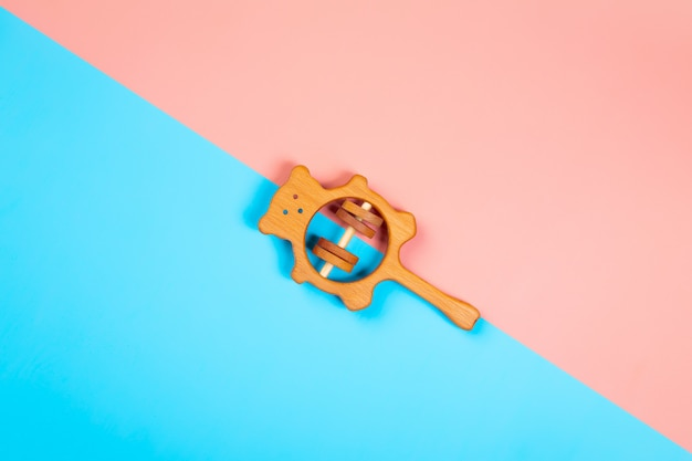 Wooden rattle bear of beech  on an isolated multicolored vibrant geometric background.