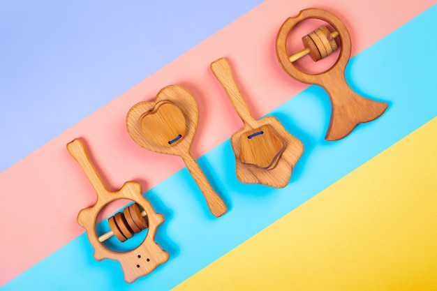Wooden rattle fish, bear,heart, star of beech  on an isolated multicolored vibrant geometric background.