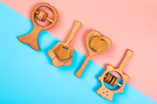 Wooden rattle fish, bear,heart, star of beech  on an isolated multicolored vibrant geometric background