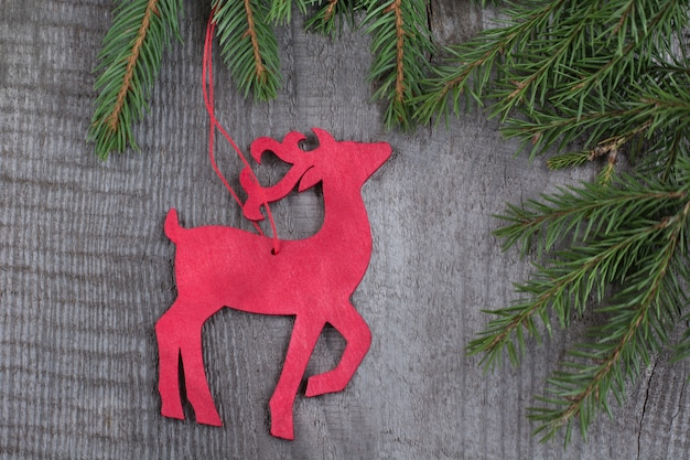 Wooden red christmas deer on wooden board.