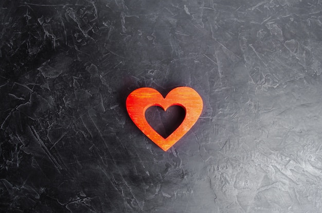 Wooden red heart on a gray concrete background.
