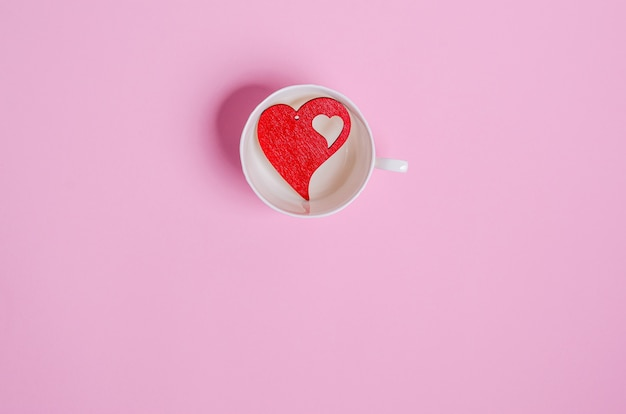 Wooden red heart in a white cup on pink