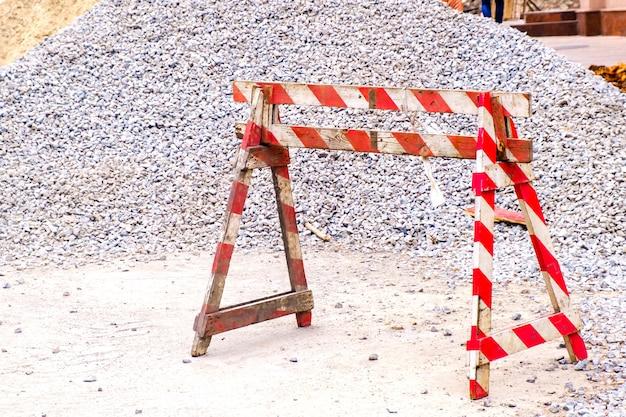 Деревянный красно-белый ограждение контрольно-пропускной пункт и кучу щебня на строительство дорог на улице города.