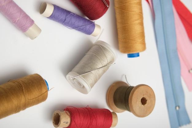 無地の背景に糸と木製リール。着色
