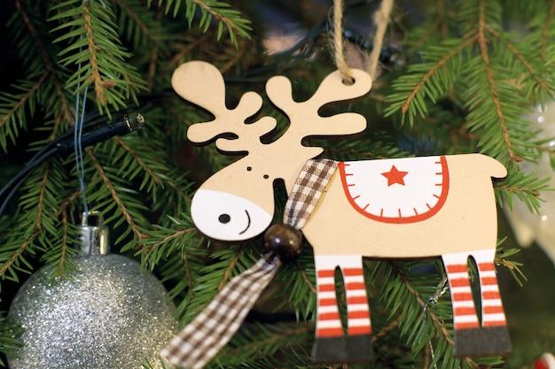 他のおもちゃの隣のクリスマスツリーに木製のトナカイのおもちゃ