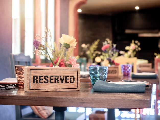 Wooden reserved sign on dining table in restaurant.