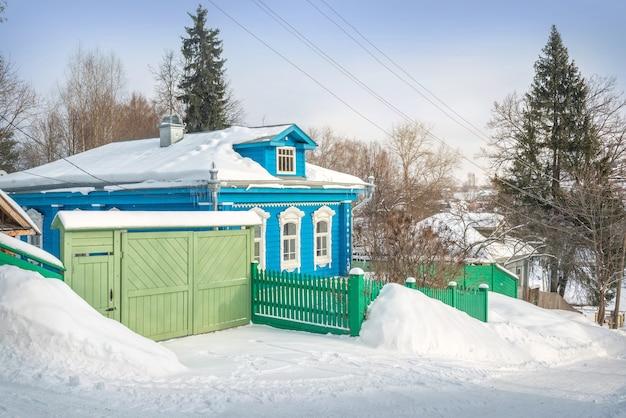 푸른 하늘 아래 겨울 날에 비추어 plyos의 산 중턱에 목조 주거용 건물 및 게이트