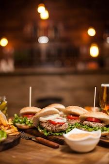 맛있는 버거와 감자튀김으로 가득한 나무 레스토랑 테이블. 클래식 버거. 마늘 소스.