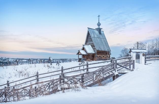 Деревянная церковь воскресения на горе левитан в плесе в снегу в свете заходящего зимнего солнца.
