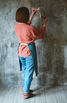 앞치마에 needlewoman의 여성 손에 핑크 폴카 도트 브레이드와 나무 복고풍 릴