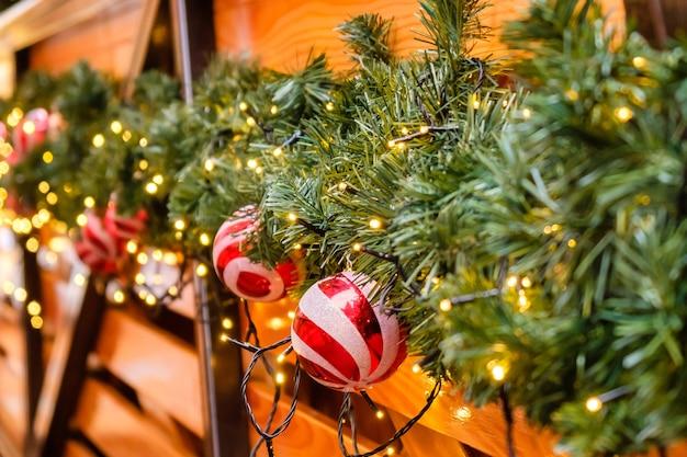 조명 화환과 많은 빨간색과 흰색 크리스마스 공, 겨울 날, 눈이없는 인공 전나무 나무로 장식 된 목조 복고풍 레스토랑 건물.