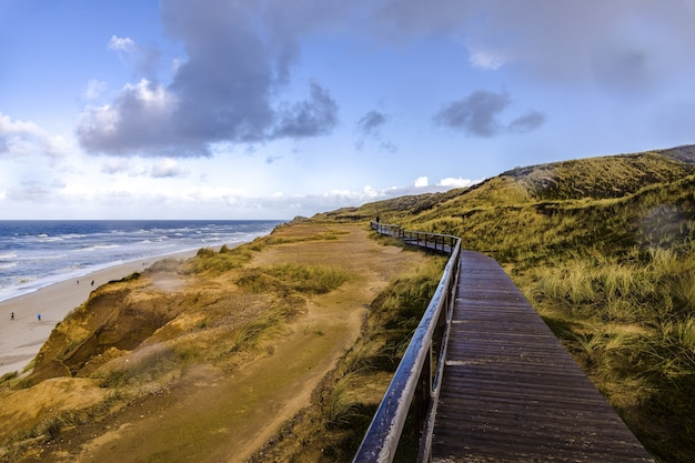 Wooden road on the red cliff near the beach in sylt, germany