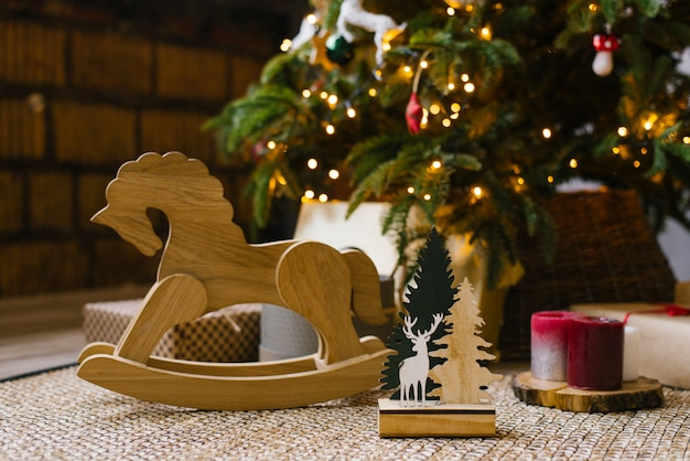 A wooden rocking horse for children stands next to christmas gifts under a christmas tree with lights