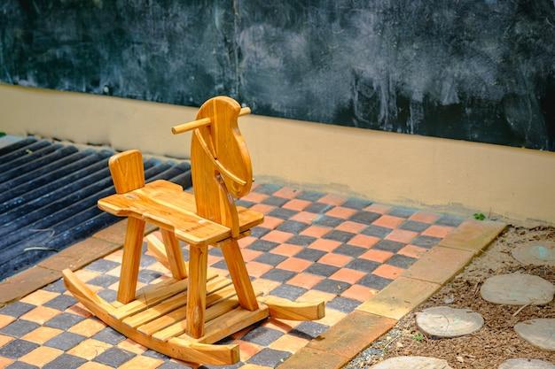 Деревянная лошадка-качалка из детской игровой комнаты, сидящая на солнце