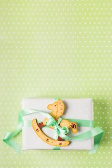 木製の揺り木馬とプレゼントボックスをグリーンのリボンで結ぶ